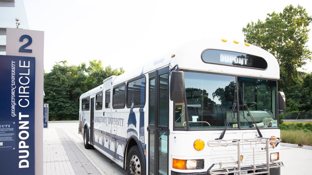 A university GUTS bus shuttle is parked in the bus turnaround.