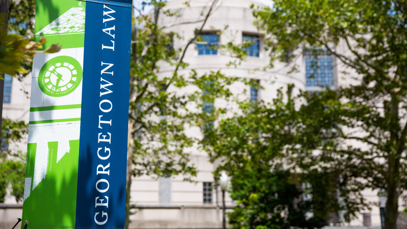 Georgetown Law banner nhangs in front of a building on campus.