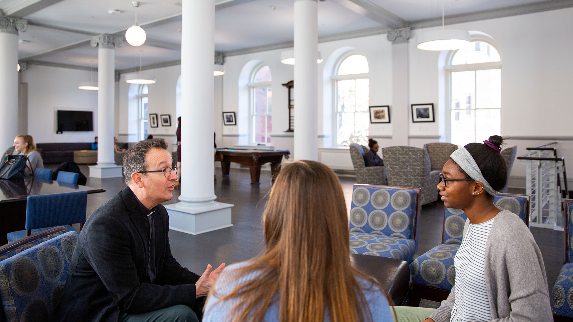 Fr. Bosco talks with students in a campus residence.