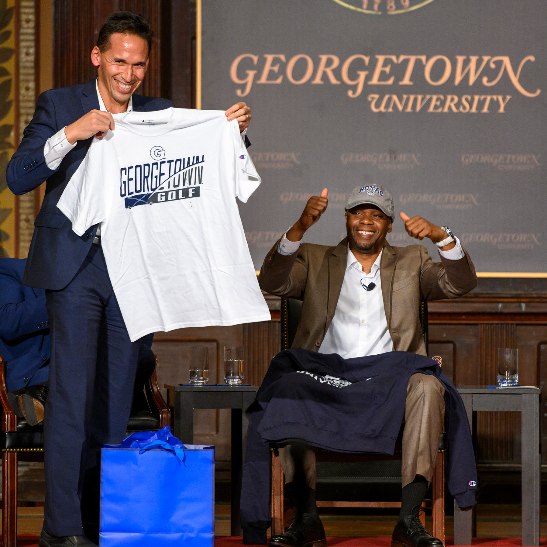 Professor Marc Howard stands on stage in Gaston Hall, presenting a Georgetown University golf t-shirt to Valentino Dixon.