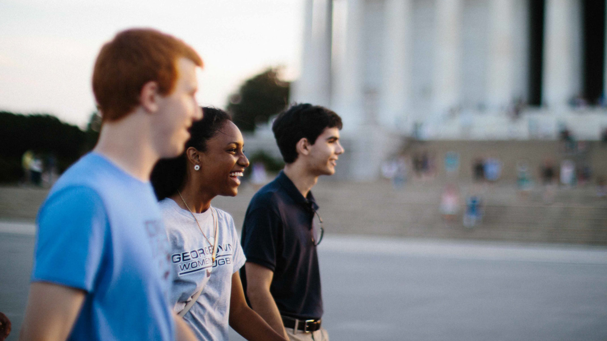 Three students walk by the monuments.