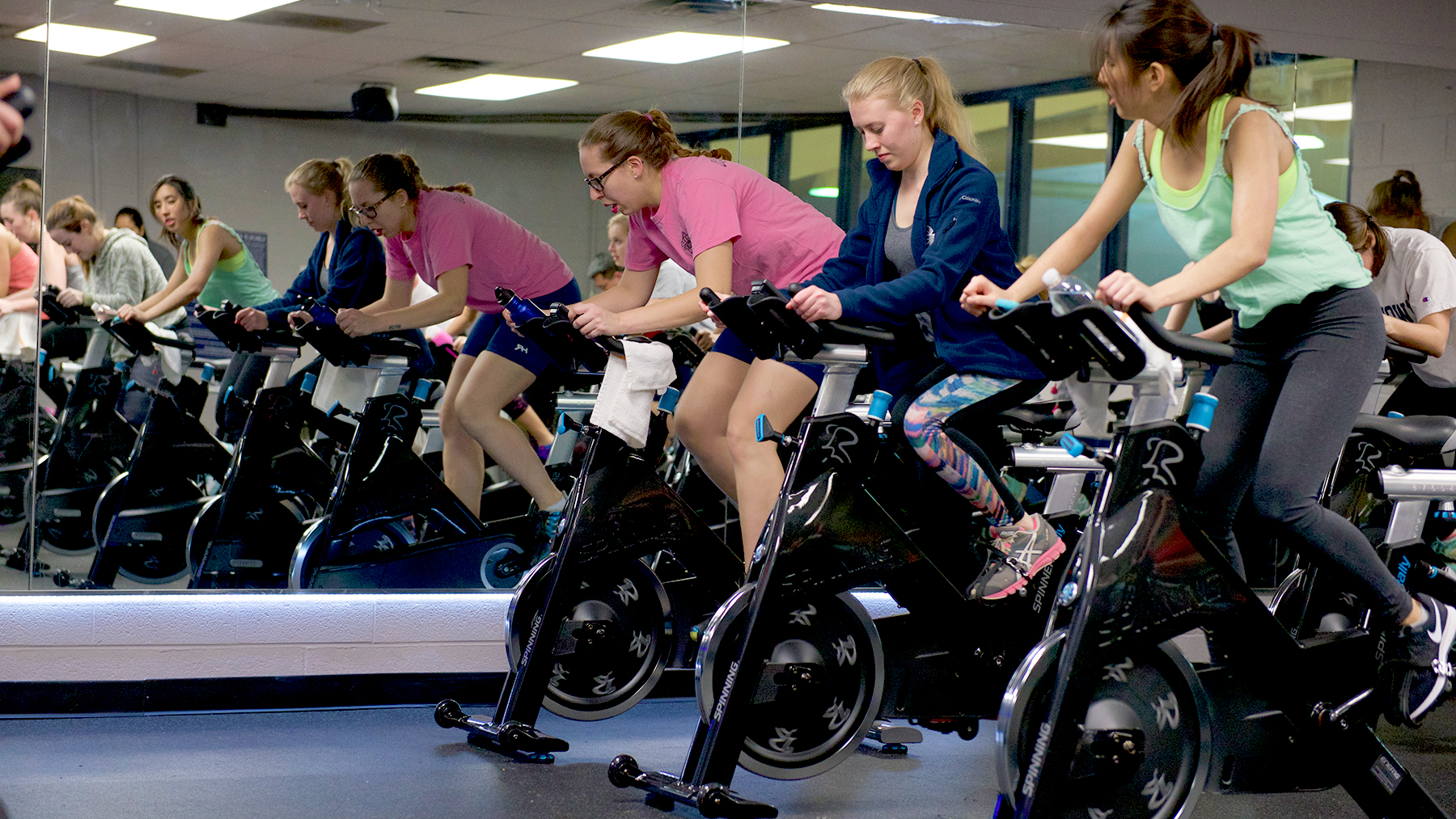 Students spin cylces in a group class in front of a mirror.