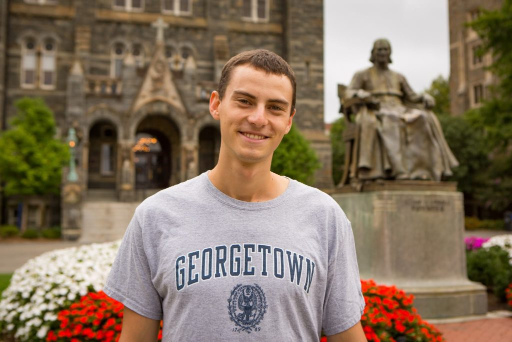 Jacob Werden stands in front of Healy Hall.