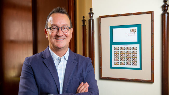 Mark Bosco stands with arms folded next to frame with Flannery O'Connor postage stamp