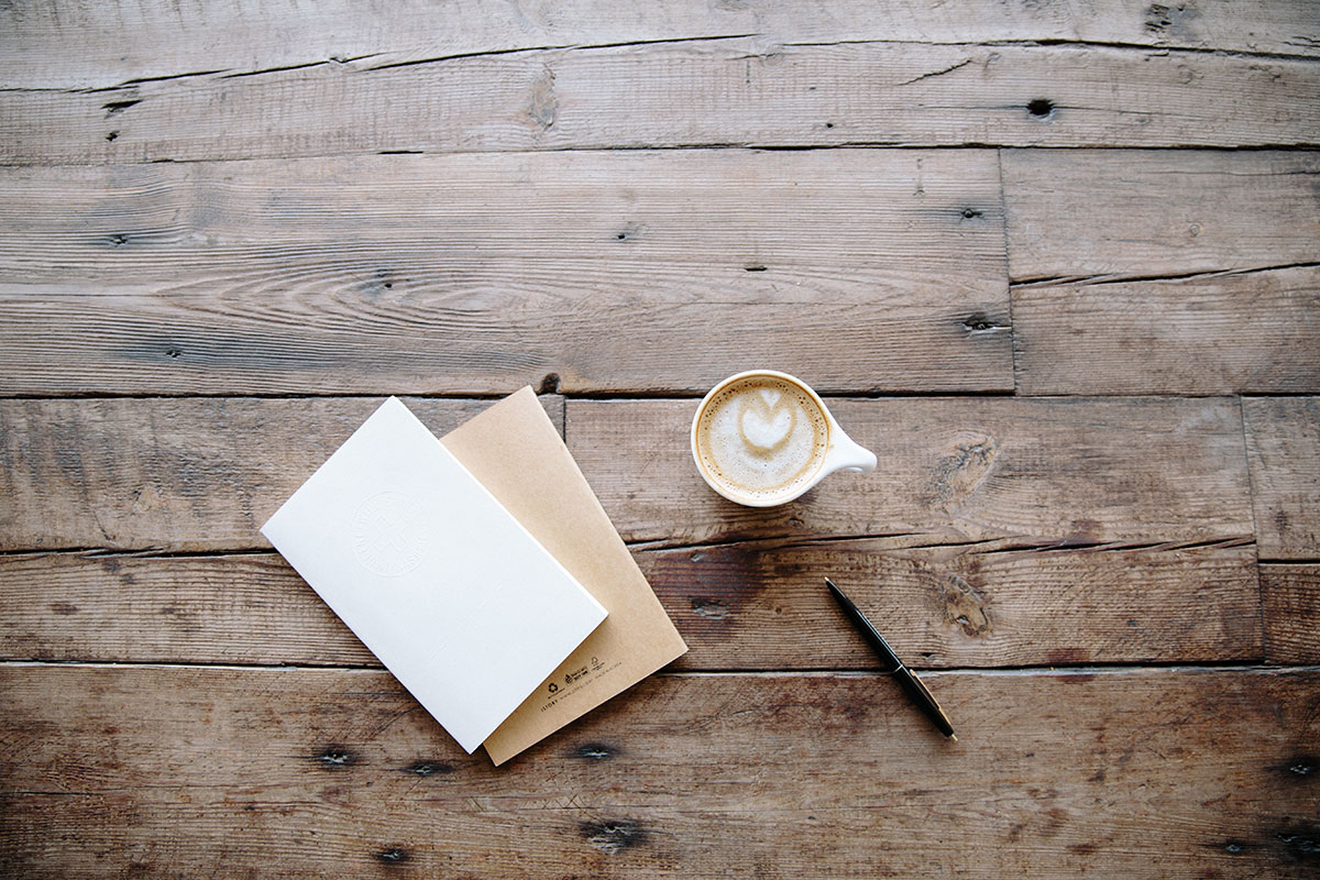 Stationary and coffee sit on a table