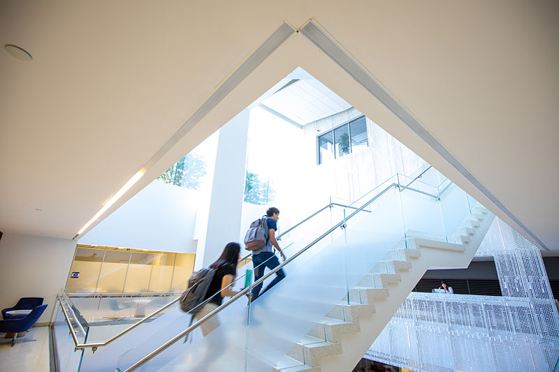 Students walk through the School of Continuing Studies lobby