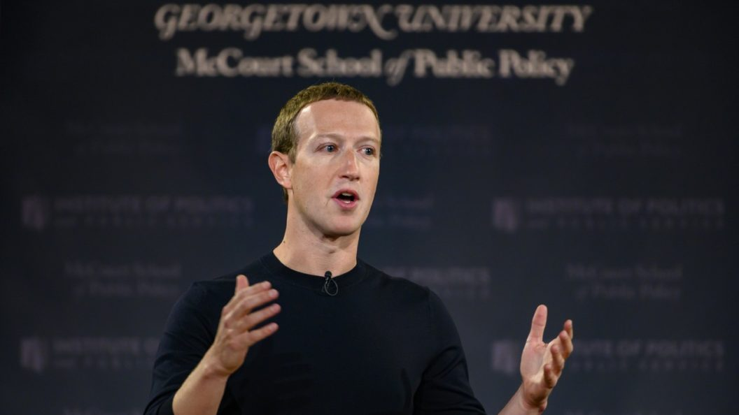 Mark Zuckerberg speaks at a lectern with a blue banner displaying