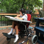 Sean Pelzel in a wheelchair on a porch outside