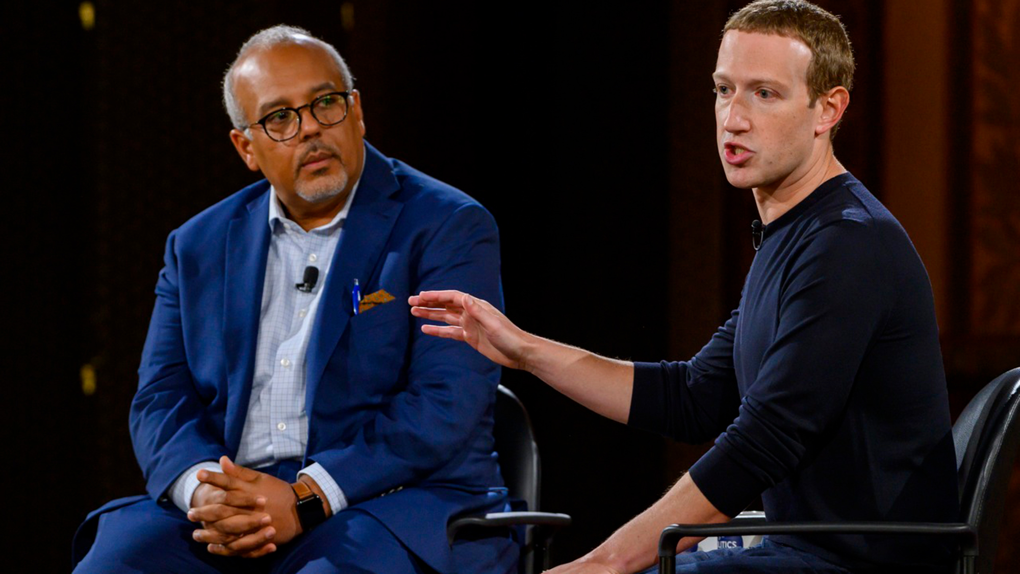Mo Elleithee and Maerk Zuckerberg talk while seated on the stage.