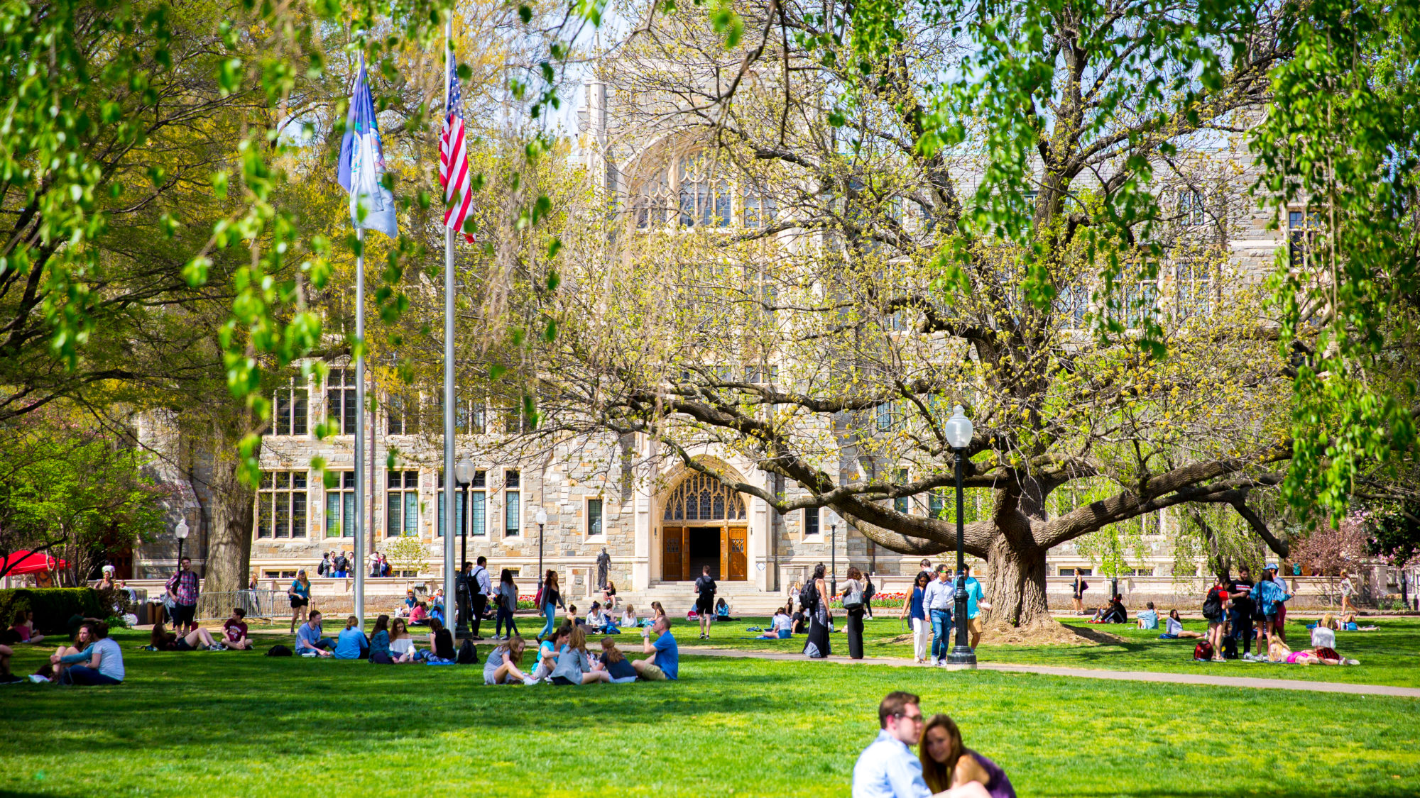 Students lounge on Copley Lawn in front of White Gravenor.