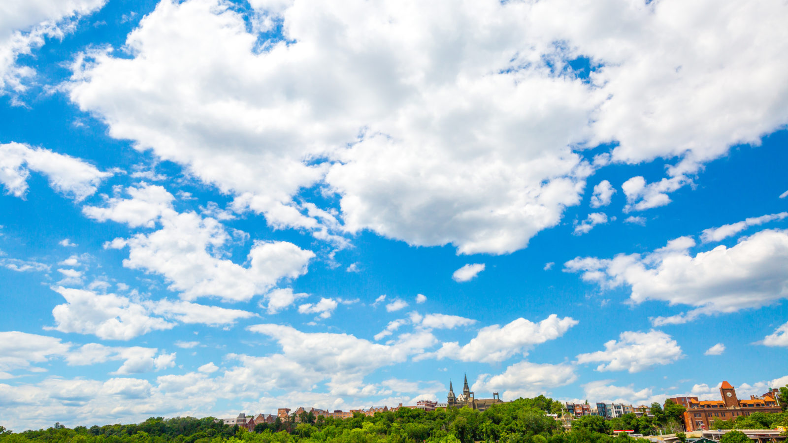 The Georgetown University campus outlines the bottom half of the photo, and is framed by a large, blue sky.