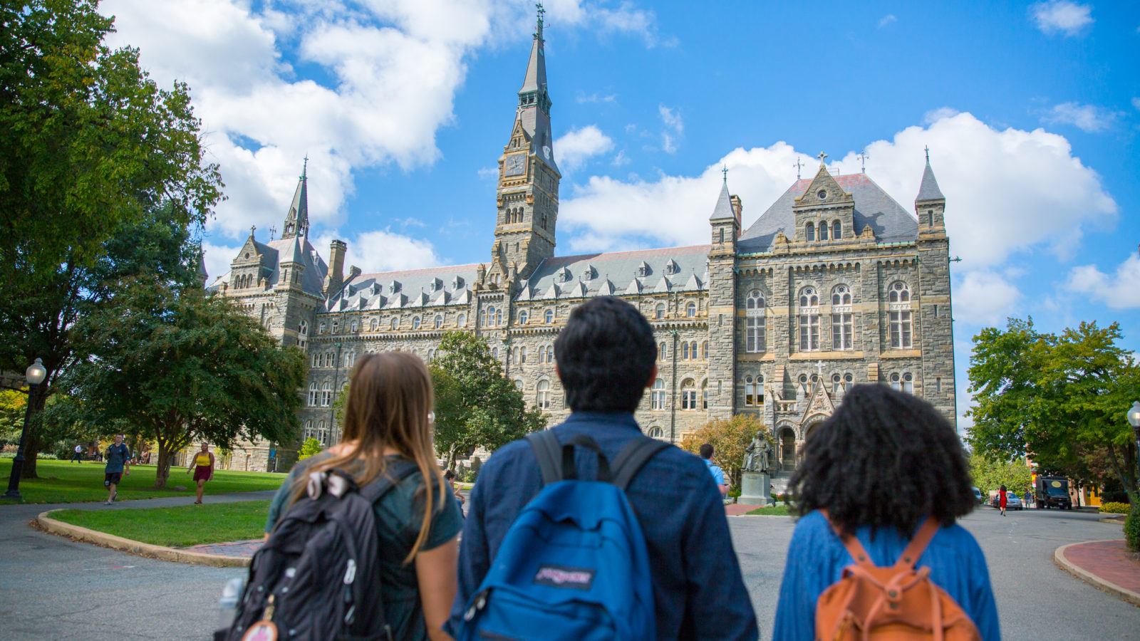 Three undergraduate students are walking towards Healy Hall. The backs of their heads and backpacks are visible as they walk towards the building.