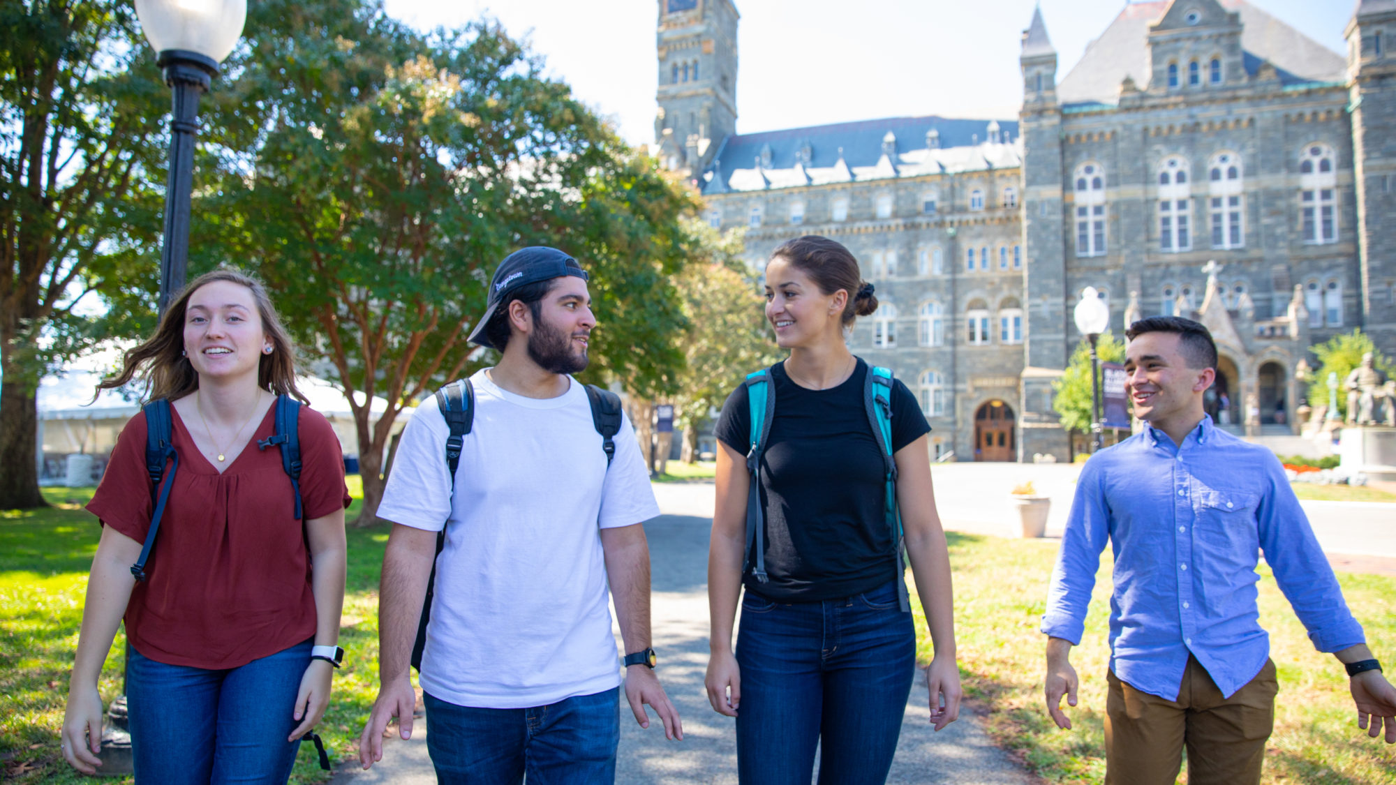 Four students with backpacks talking and walking through campus.
