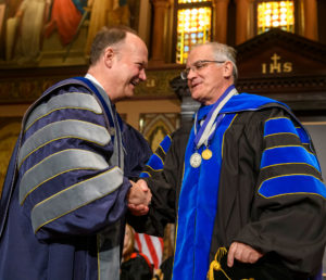 John J. DeGioia shakes the hand of Italo Mocchetti on stage while they are both dressed in academic regalia.