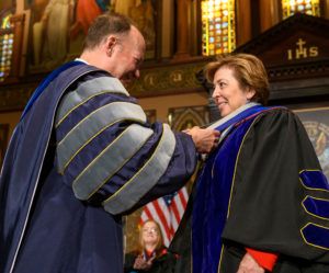 John J. DeGioia shakes the hand of Cristina Sanz on stage while they are both dressed in academic regalia.