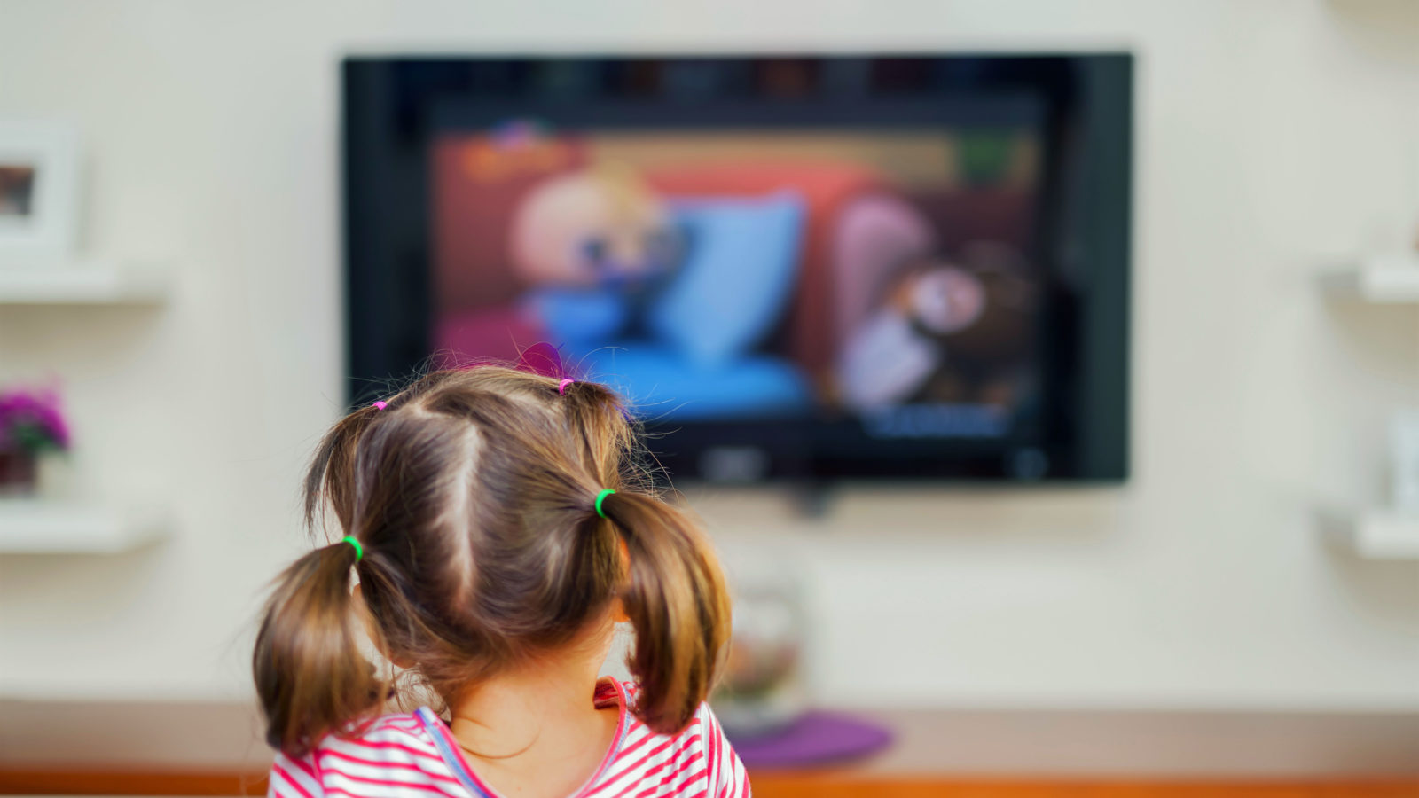 A little girl facing a TV showing a children's program