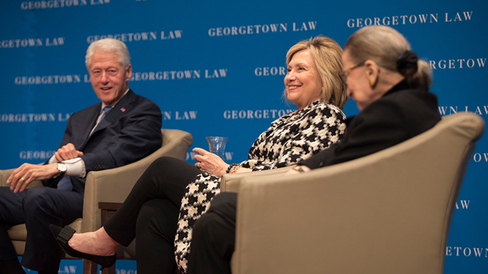 Bill Clinton and Hillary Rodham Clinton sit with Ruth Bader Ginsburg on stage with Georgetown Law signage in the background.