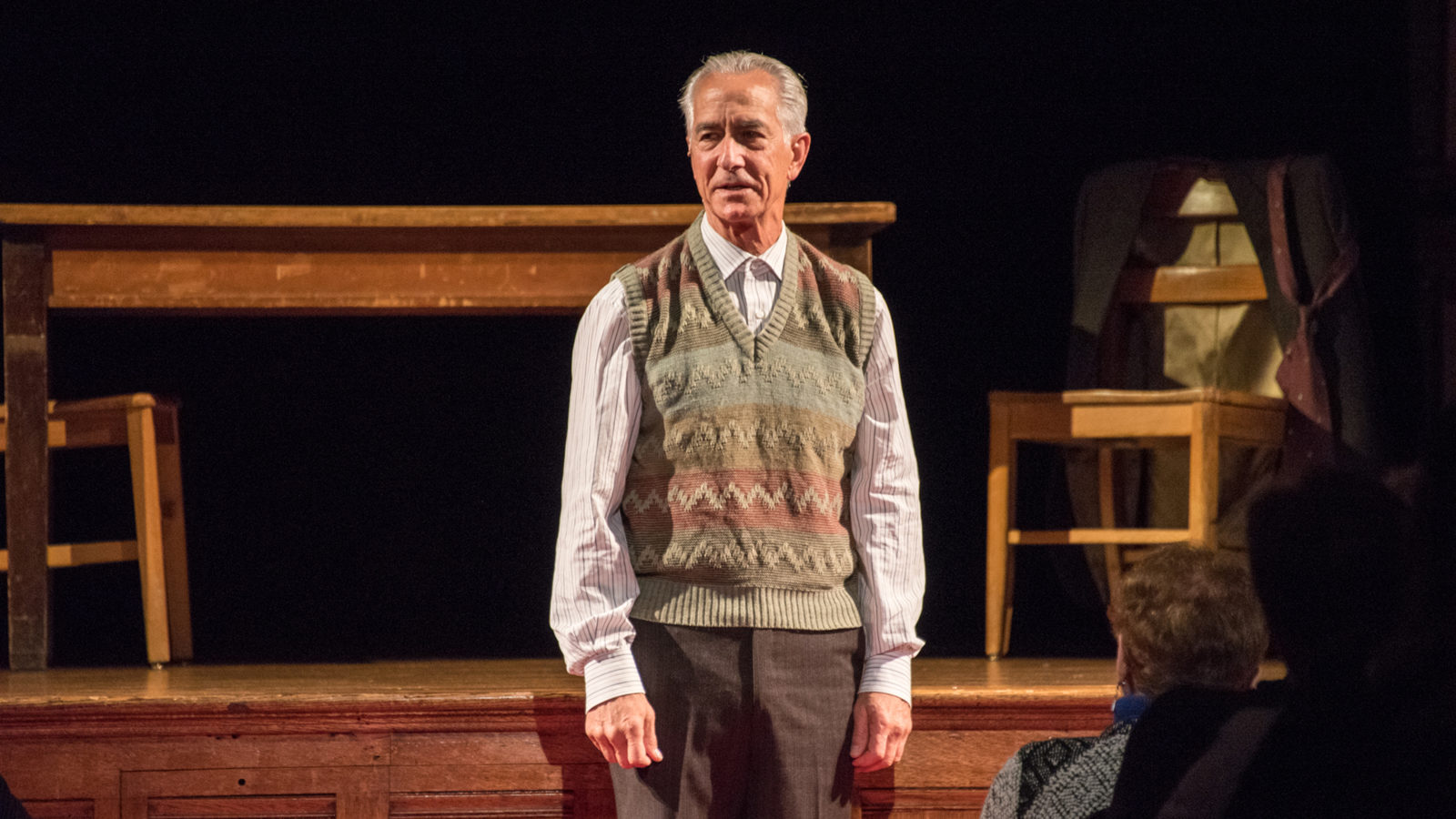 David Strathairn on stage with a desk and chairs playing Jan Karski