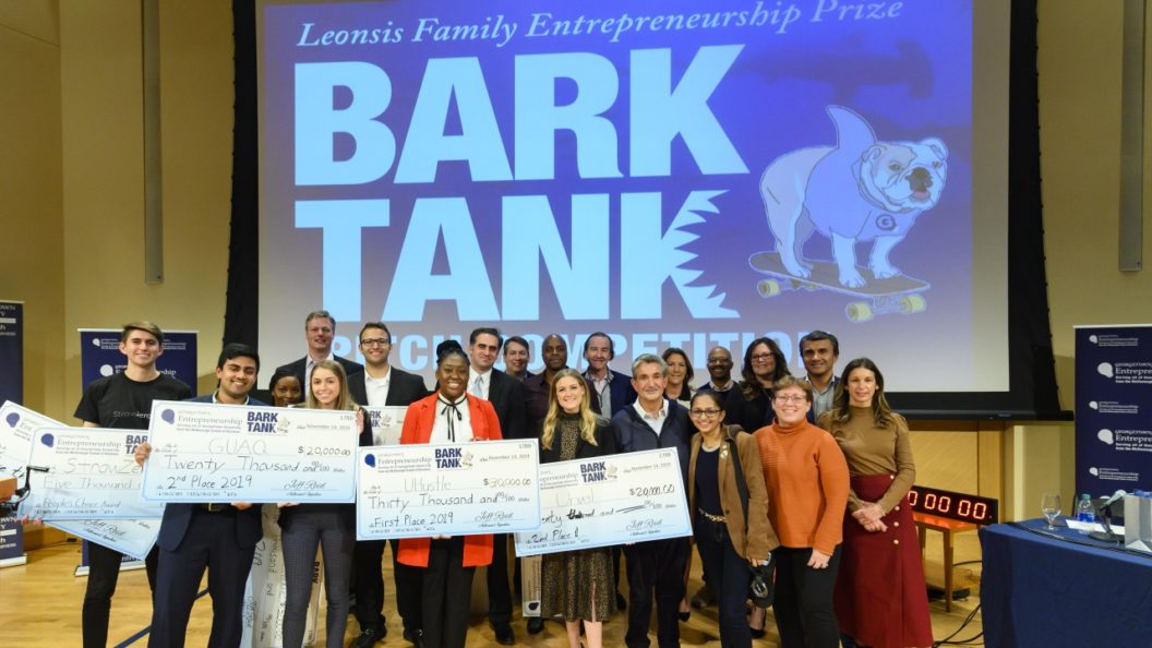 Students stand with oversized checks, Ted Leonsis and professors on a stage with a large screen reading Bark Tank and an illustration of Jack the Bulldog