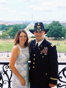 Christopher and Betsey Mercado stand beside each other outside with the Washington Monument off into the distance.