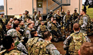Christopher speaks to his squadron all dressed in camouflage..