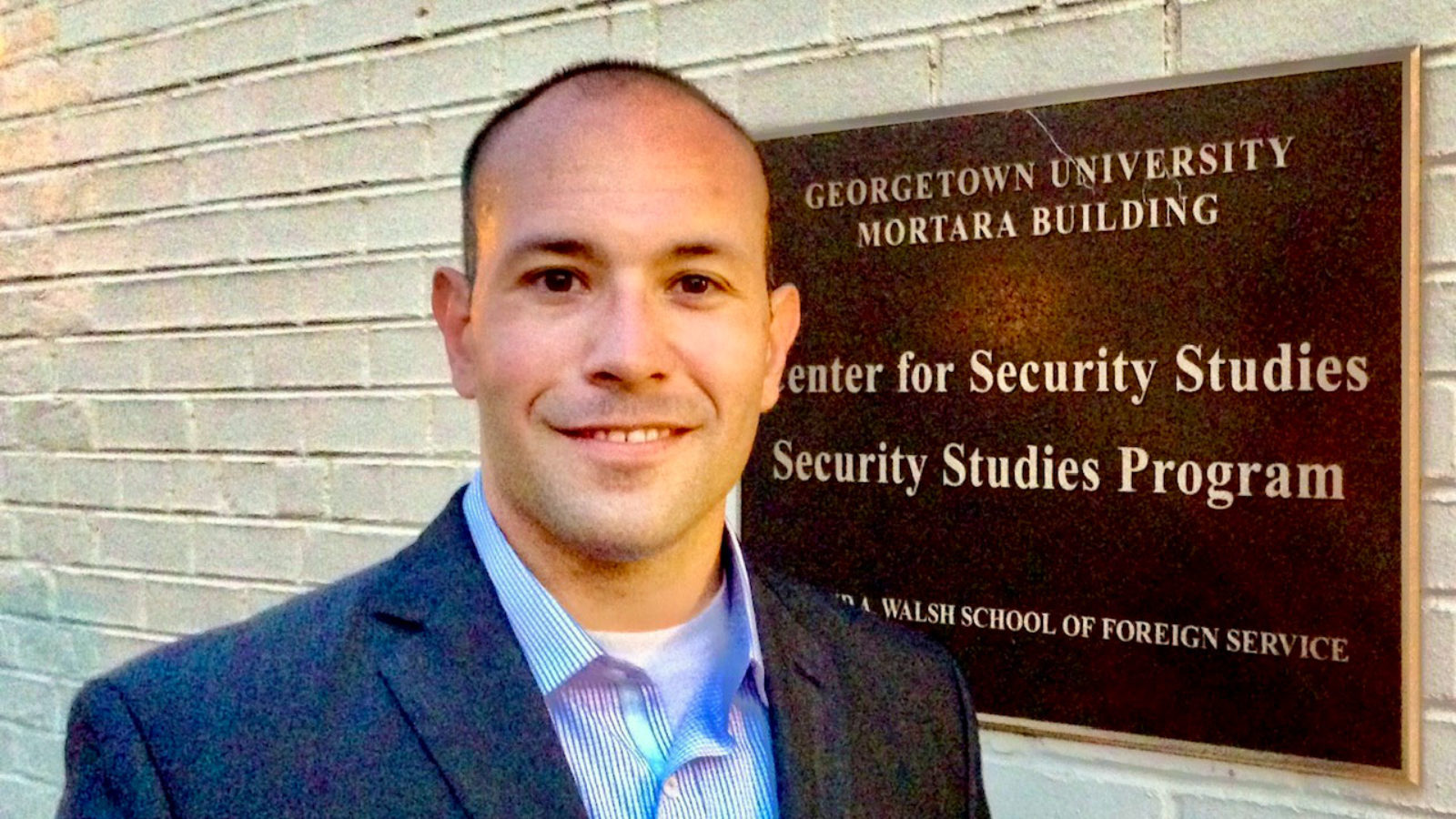 Chris Mercado stands near the Peace and Security Studies building plaque.