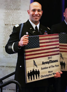 Christopher Mercado stands with his Army Times Soldier of the Year Award.