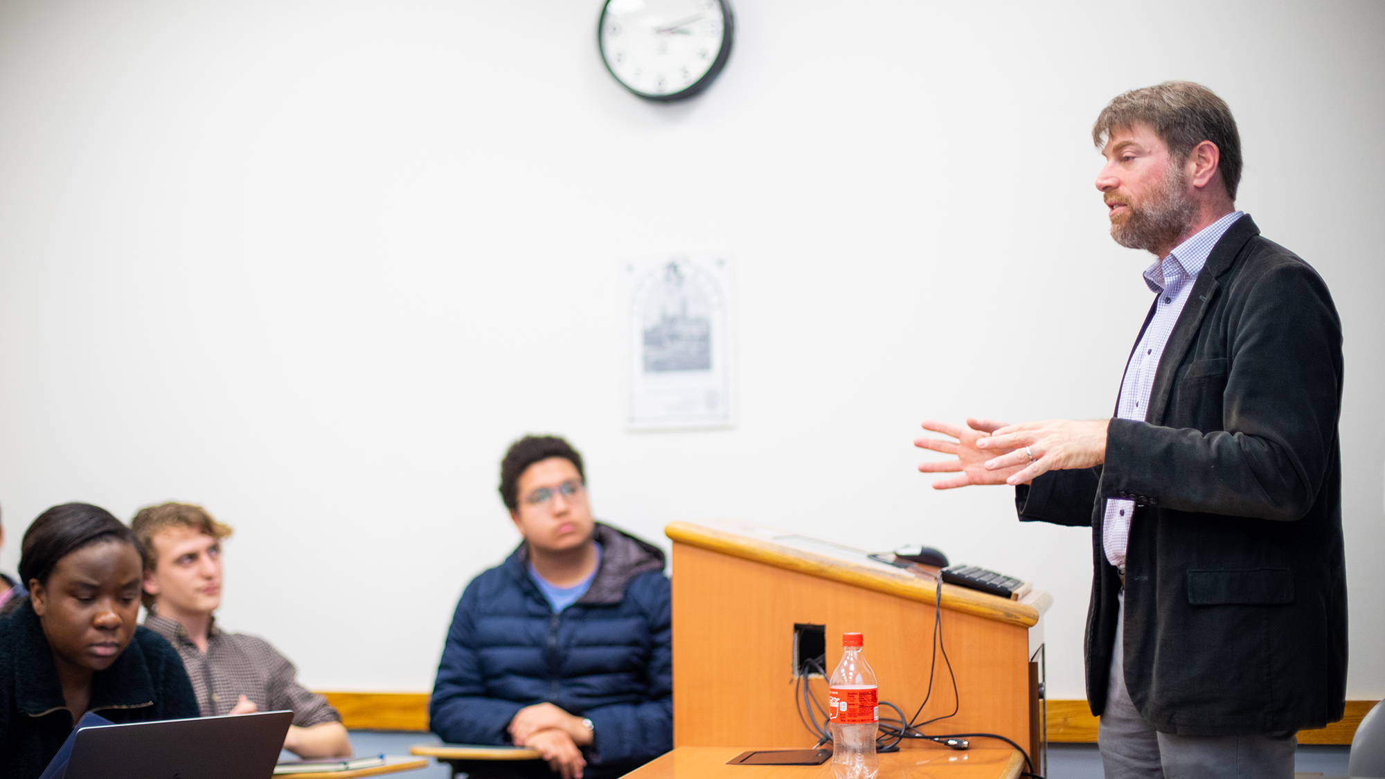 Adam Rothman gestures standing near a podium in a classroom with three students listening