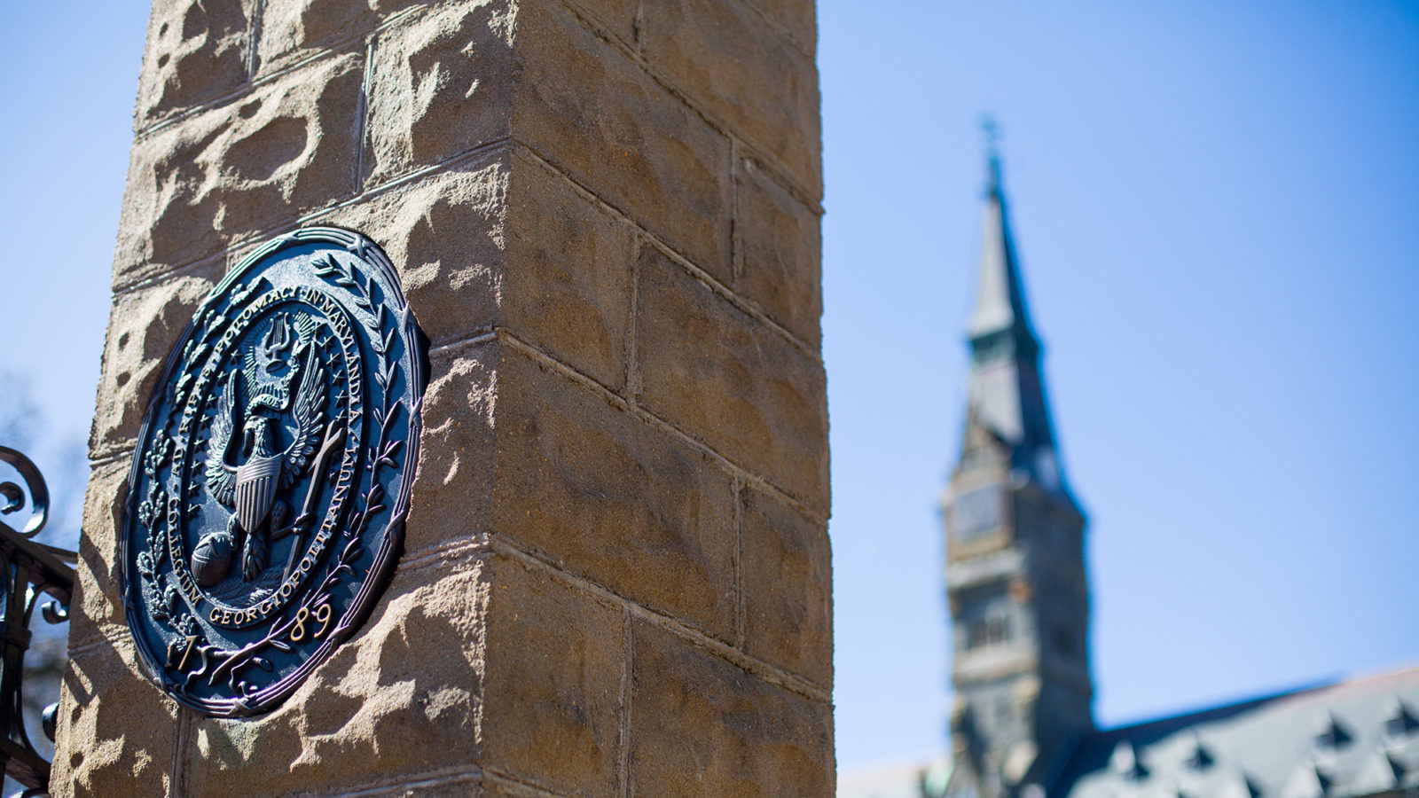 Front gates showing Georgetown seal on stone column with Healy building in the background