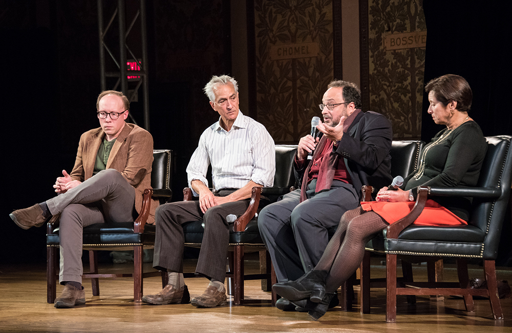 Clark Young, David Strathairn, Derek Goldman and Cynthia Schneider sit onstage in Gaston Hall with Goldman holding microphone