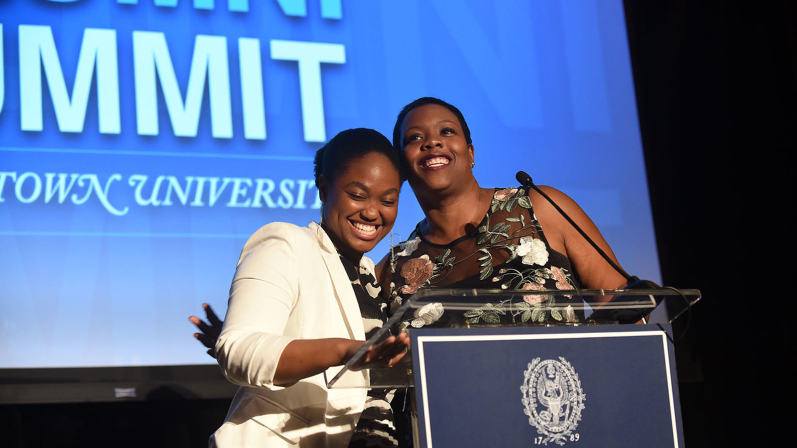 Elizabeth Nalunga and Kaya Henderson embrace at the lectern on stage with Black Alumni Summit signage on a blue background.