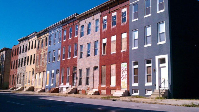 Five colorful, abandoned rowhomes stand side-by-side along a quiet street.