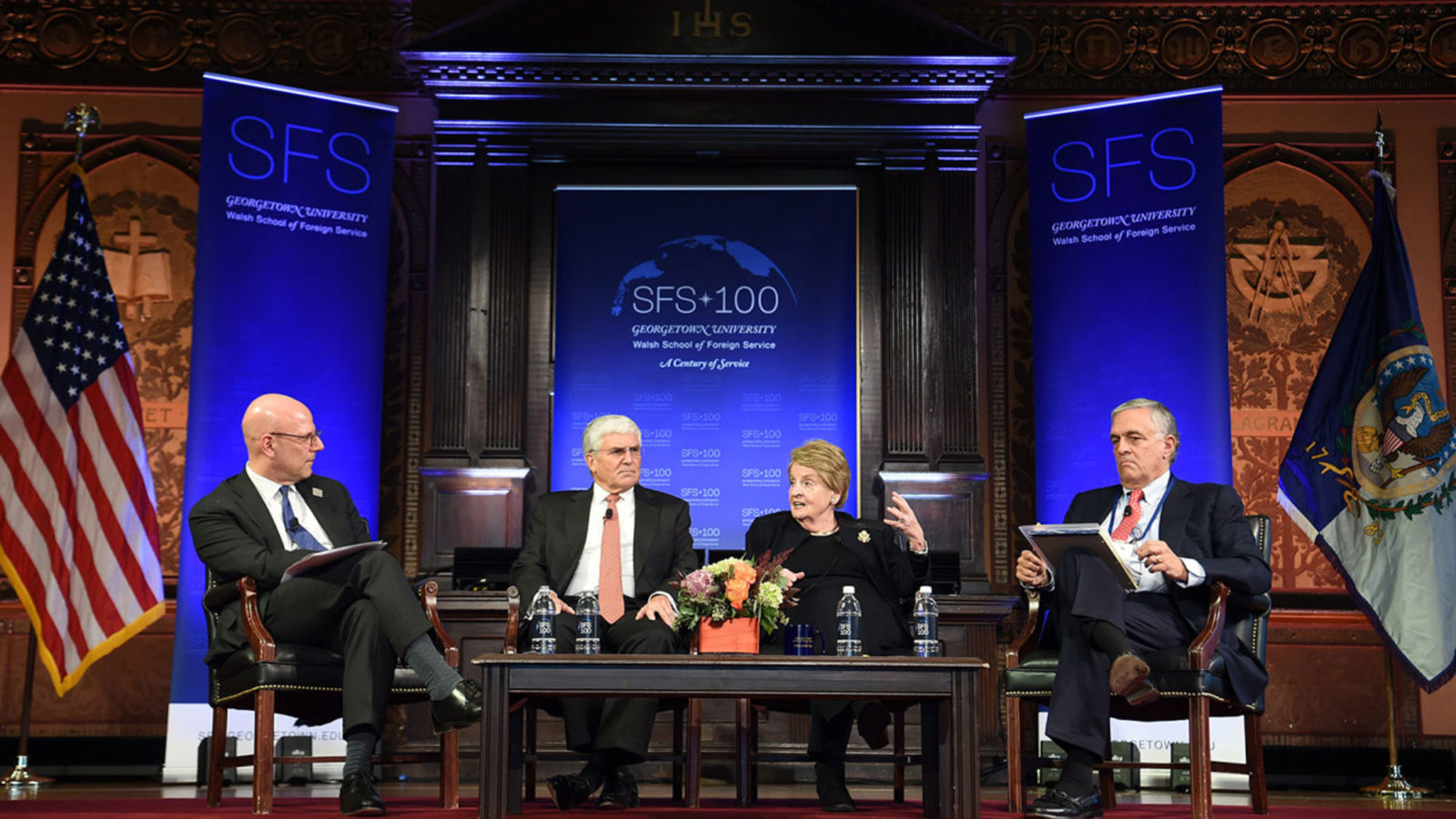 Joel Hellman, George Casey, Madeleine Albright and George Tenet sit on stage in Gaston Hall with blue SFS 100 banners in the background.