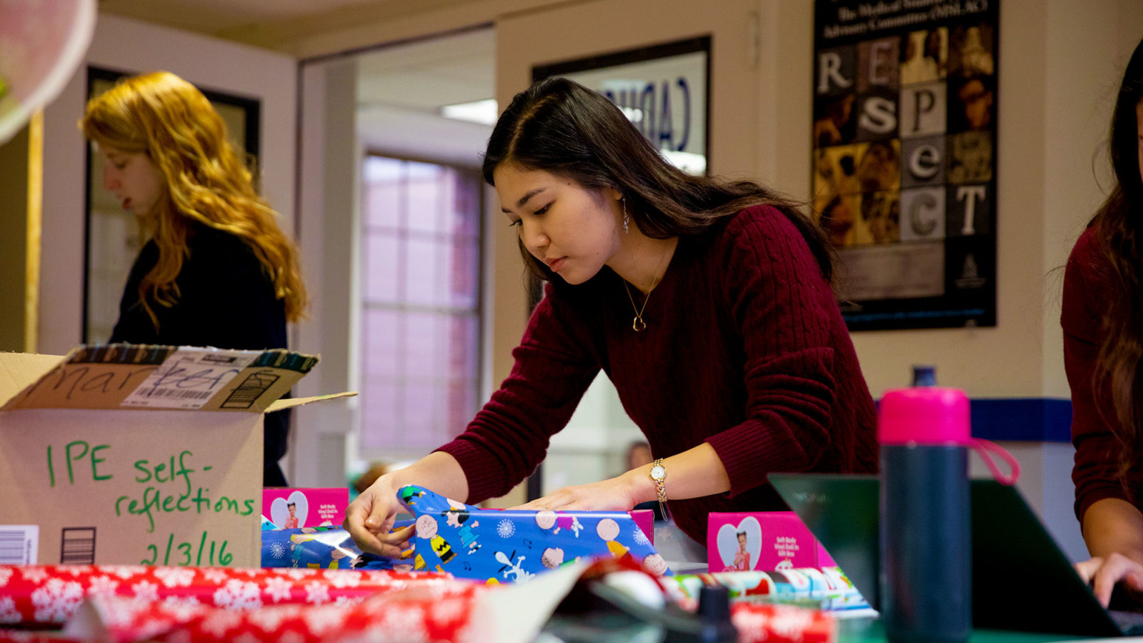 A female student wraps Christmas gifts.