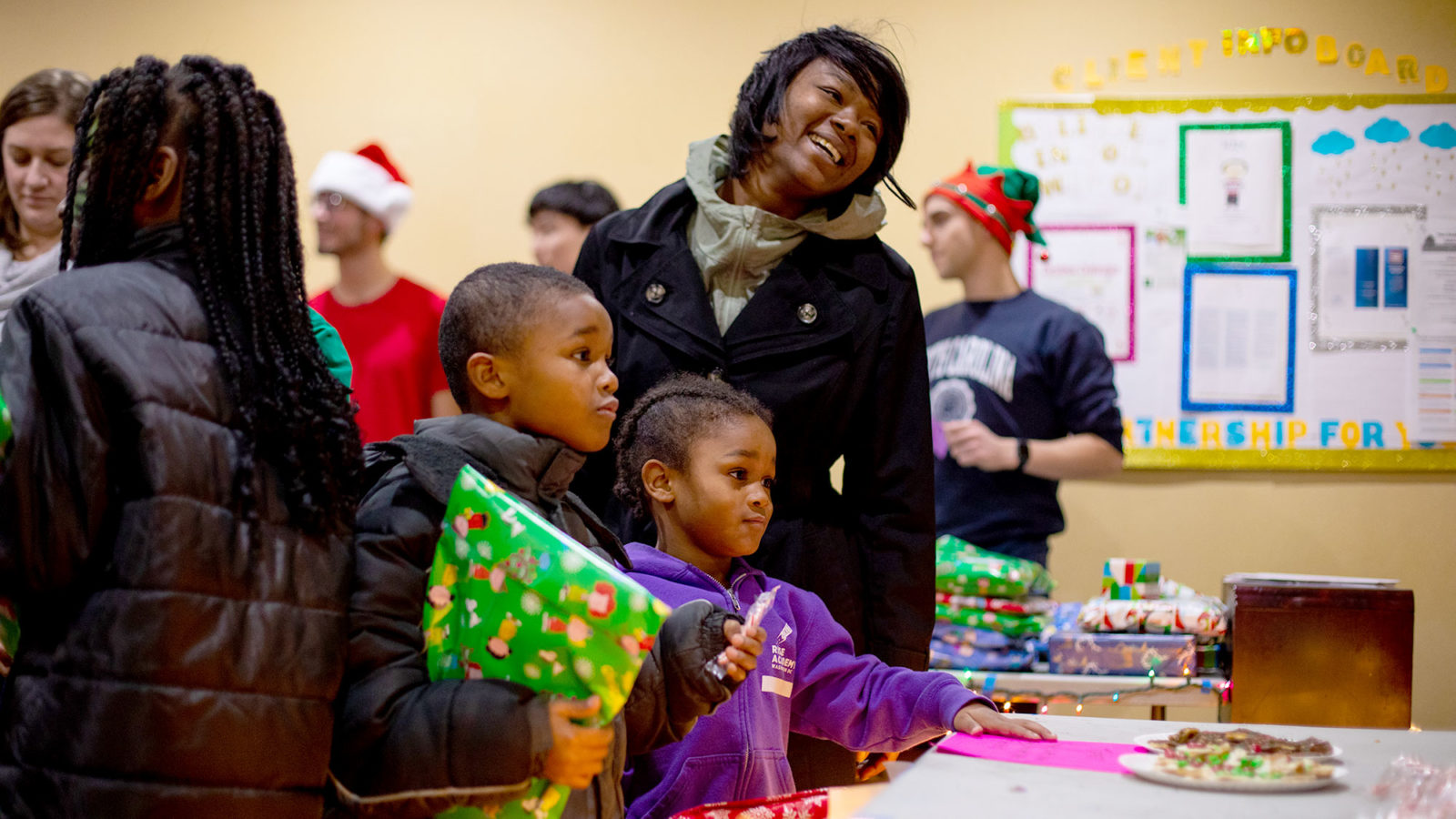 A woman smiles with her two children as they hold wrapped Christmas presents.