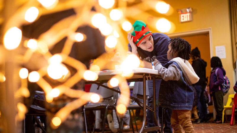 A student wearing a Christmas hat leans down to talk to a child with decorative lights in the foreground.