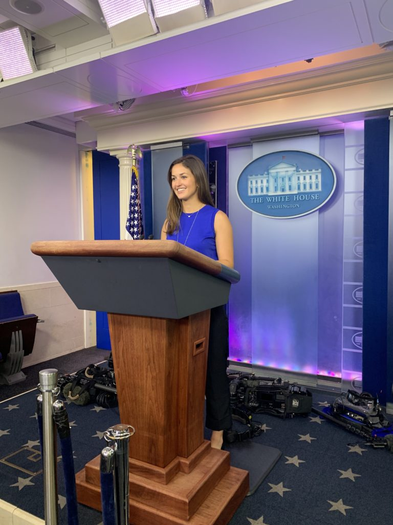Student smiles while standing behind a podium in the White House briefing room.