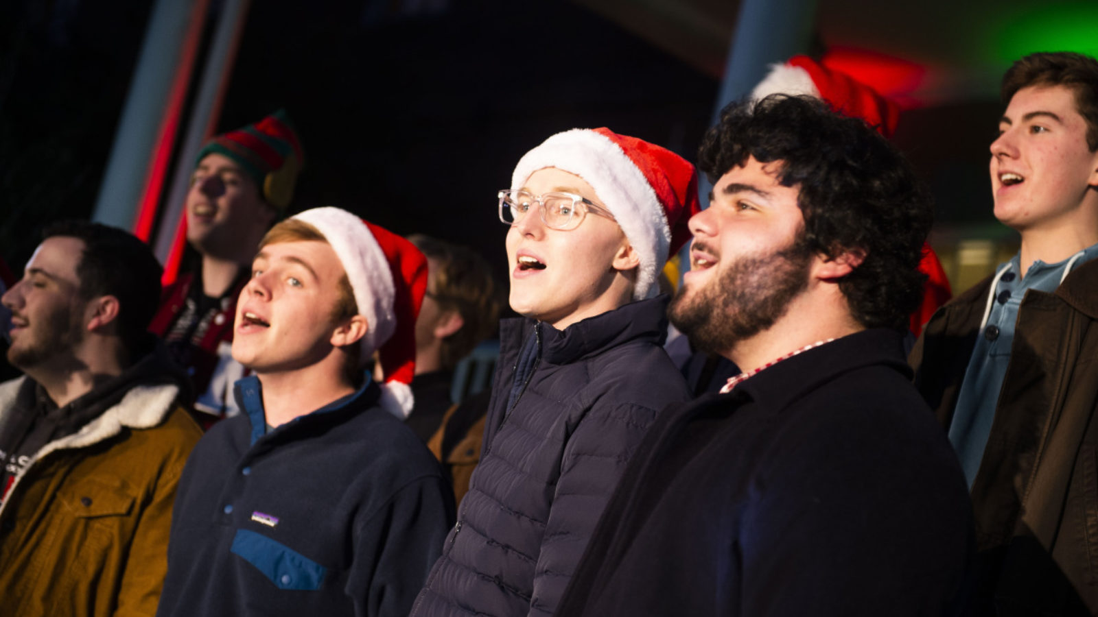 Students sing in chorus outside donning Santa hats during an evening performance.