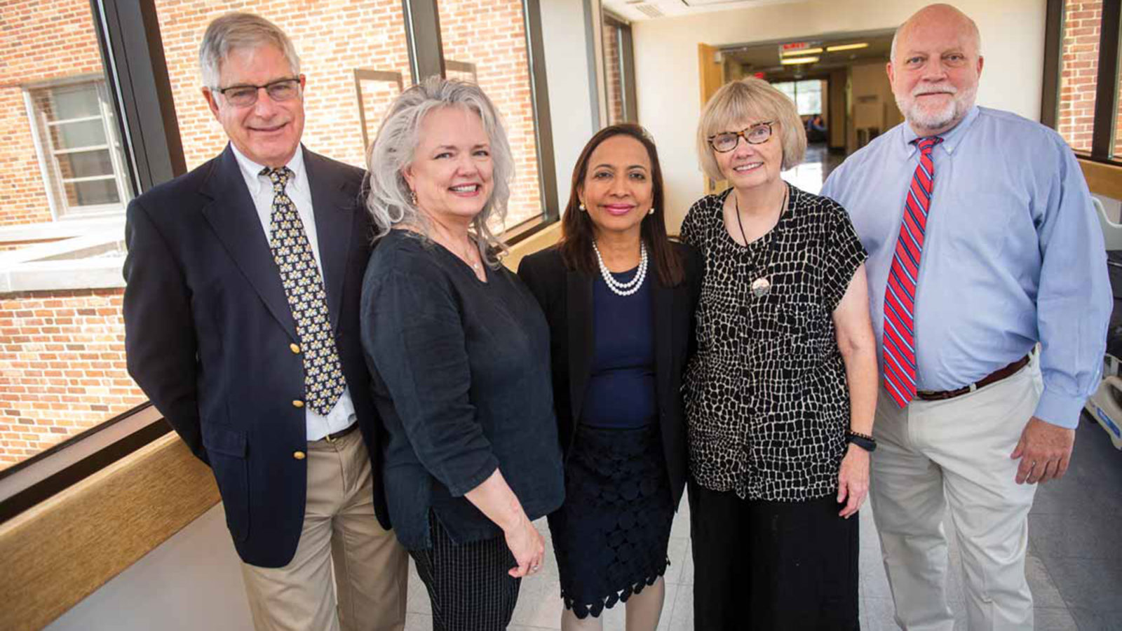 Phil Pierce, Ella Curry, Princy Kumar, Mary Young and Chip Read stand together near windows in a building.