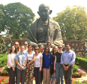 A group of people, including Kyra Kocis, in front of a statue of Gandhi.