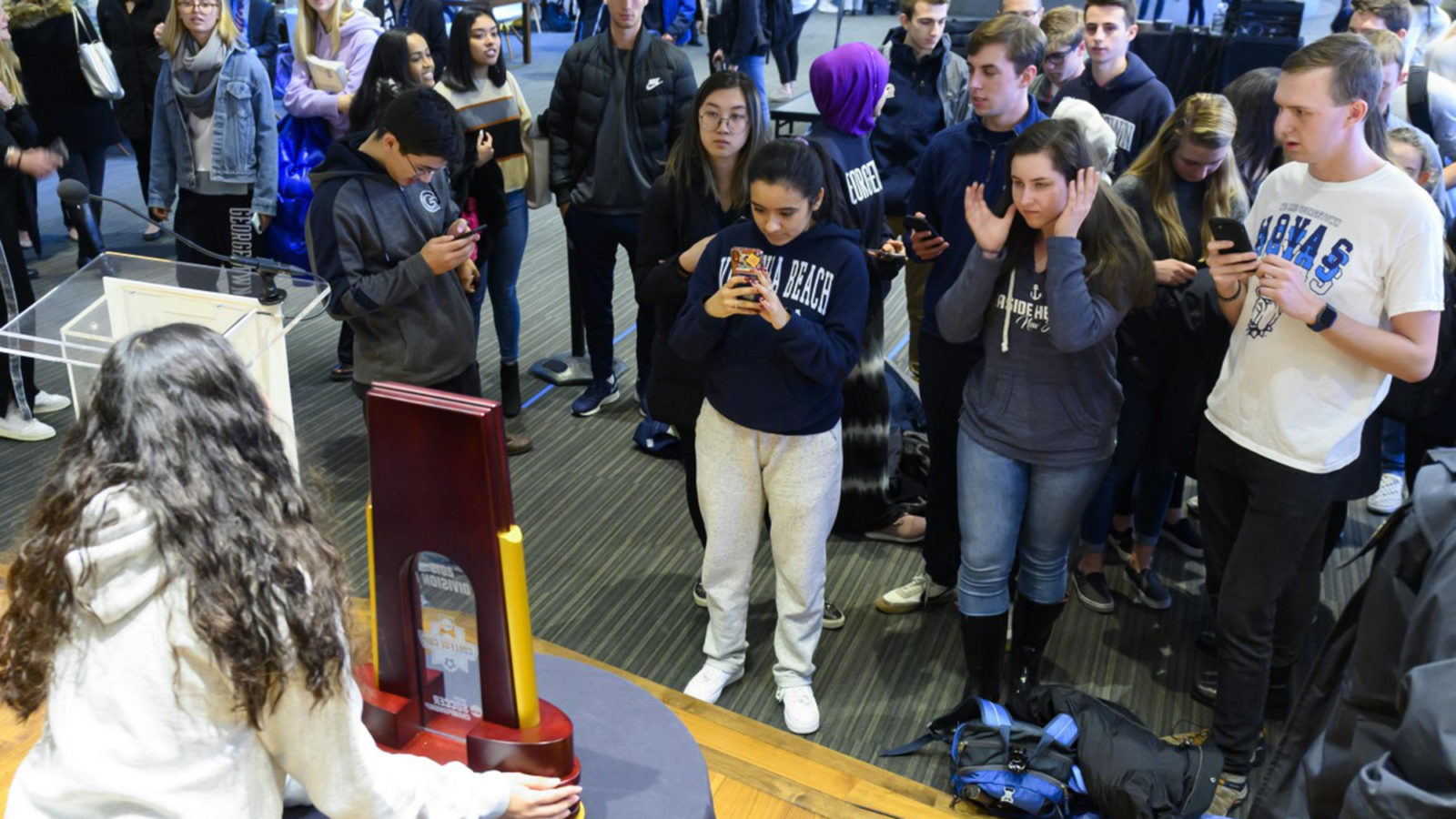 Georgetown students stand and take photos of the NCAA Championship trophy held by a woman on a stage
