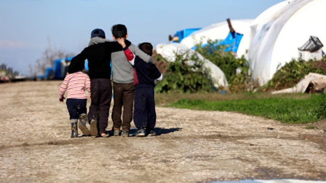 Four refugee children walking on a dirt road near tents
