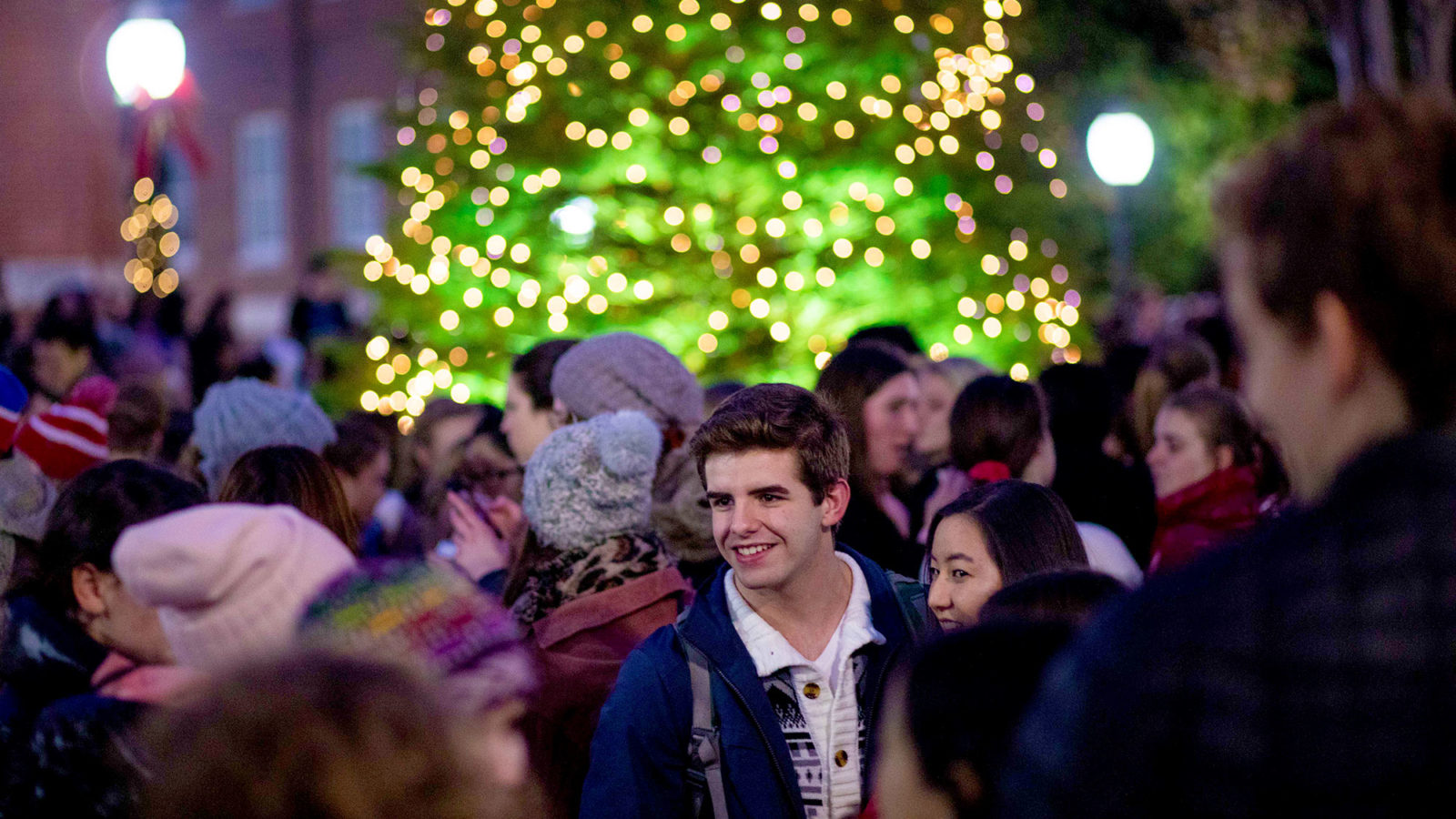 Students talk outside with a lit Christmas tree in the background.