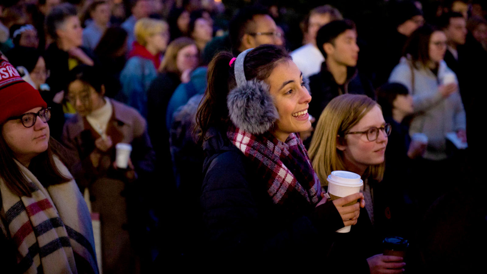 A female student looks at a performance with a smile amid a crowd of students.