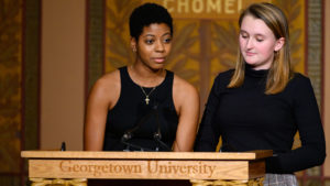 Brianna Rodgers and Lucy Chatfield stand beside one another on stage and speak at a lectern to the audience.
