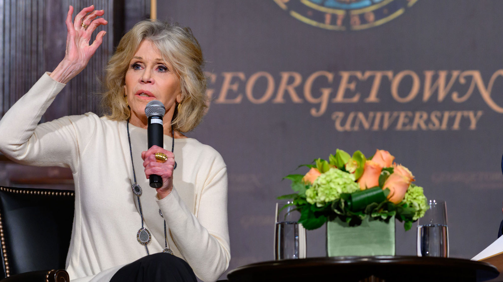 Jane Fonda raises her hand while sitting on stage.