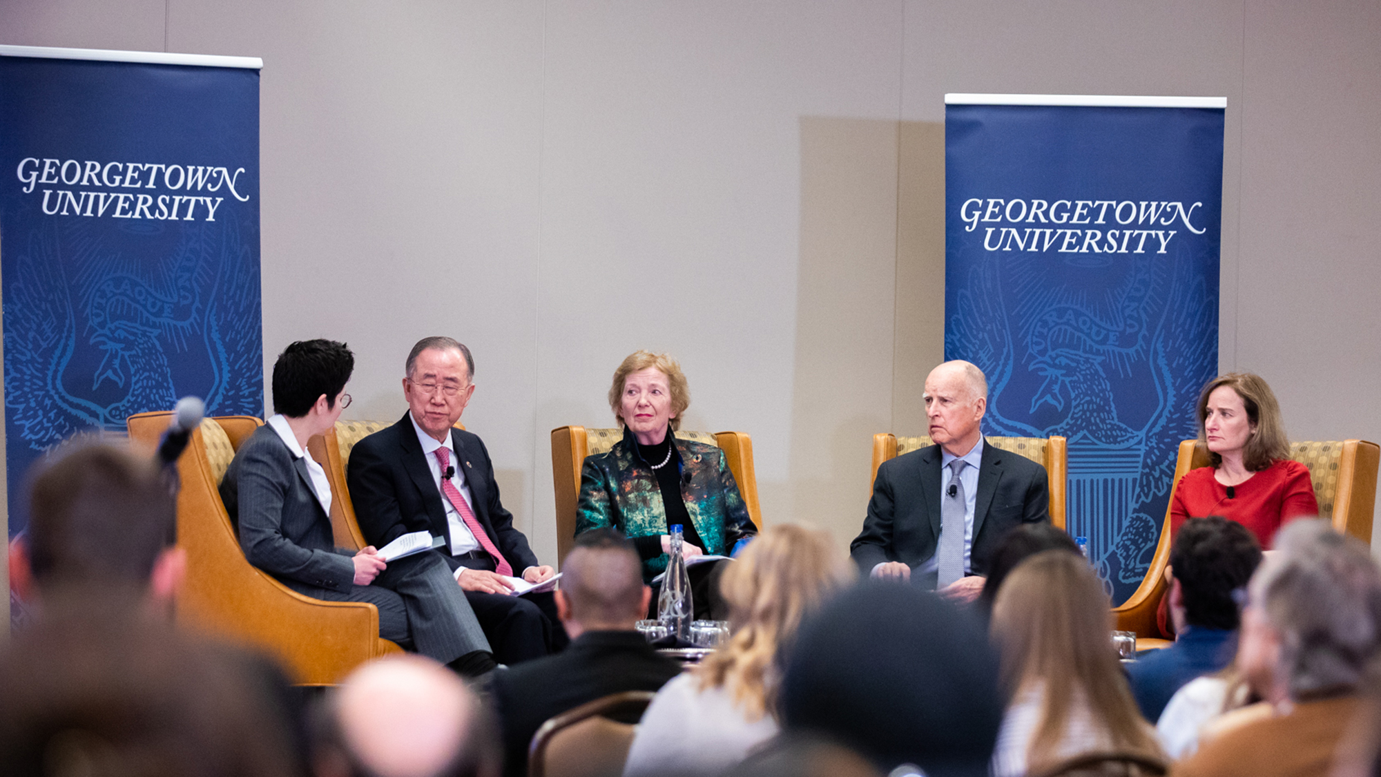 Desha Girod holds a microphone sitting next to Ban Ki-Moon, Mary Robinson, Jerry Brown and Rachel Bronson with a Georgetown University banner behind them