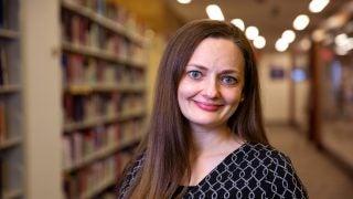 Cassandra Berman next to tall book shelves