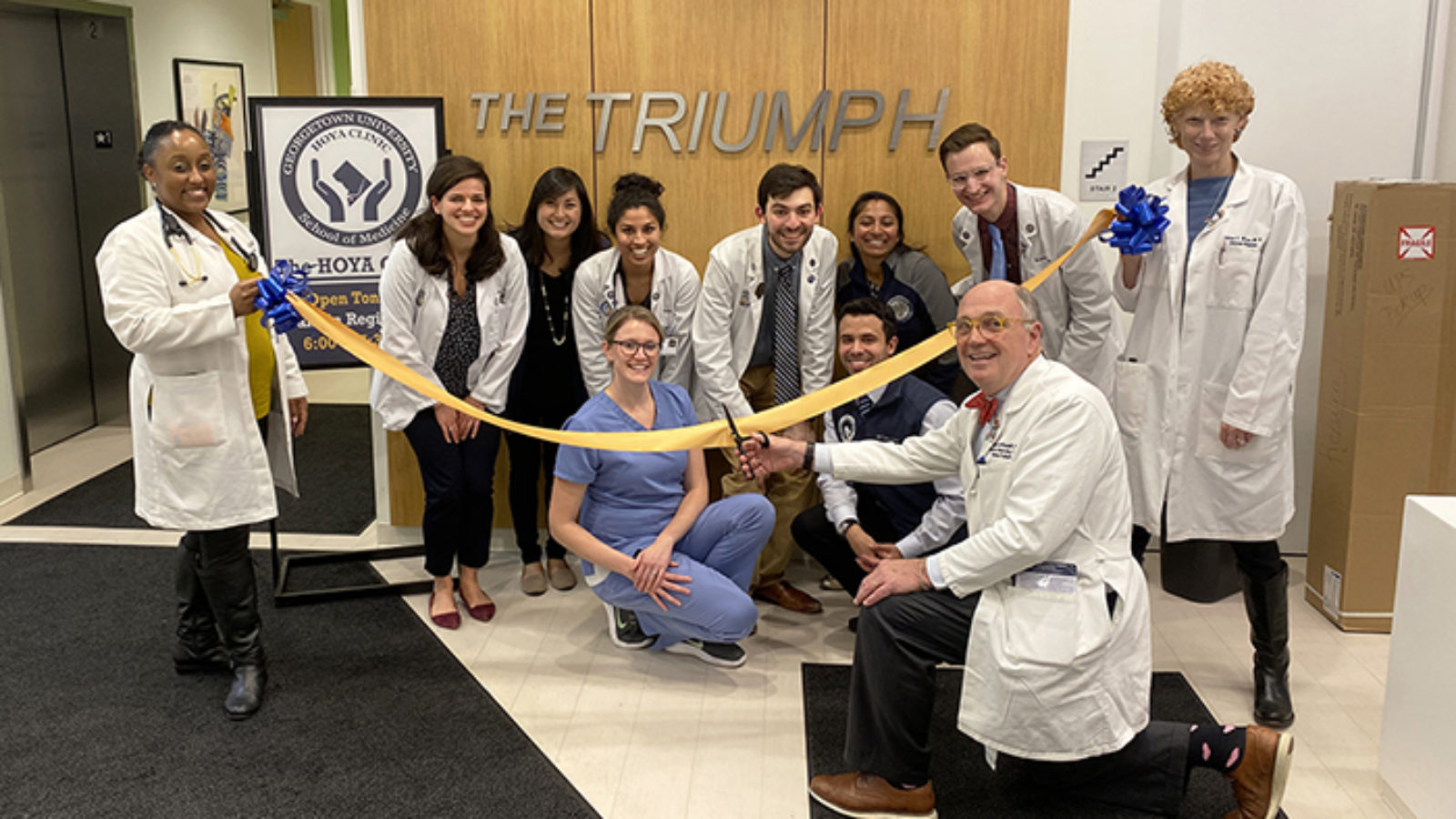 DDr. Stephen Ray Mitchell kneels on the floor cutting a yellow ribbon held by two other doctors as doctors and other people kneel or squat in front of a sign reading The Triumph
