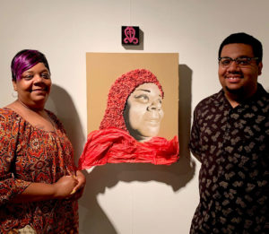 Kenlontaé Turner and Shameka Fallin stand near a piece of artwork hanging on the wall.